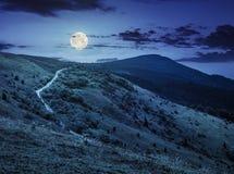 Strada attraverso il pendio di collina in alte montagne alla notte Immagine Stock Libera da Diritti