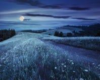 Strada attraverso il prato sul pendio di collina alla notte Fotografie Stock
