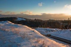 Strada attraverso le montagne di tramonto Immagine Stock