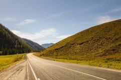 Strada attraverso un campo di erba arancio sulla steppa dell'altopiano su un fondo delle alte montagne e dei ghiacciai innevati s Immagini Stock Libere da Diritti