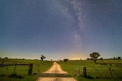 Strada aziendale attraverso un portone ed i campi alla notte in corso la Via Lattea in metà di Nuovo Galles del Sud occidentale,  Immagini Stock