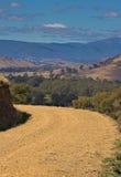 Strada aziendale non sigillata che esamina vista delle colline distanti Fotografie Stock Libere da Diritti