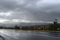 Strada bagnata con le montagne nei precedenti fotografia stock