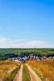 Strada campestre in cielo blu del campo di autunno Strada campestre attraverso i campi Immagini Stock