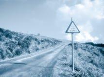 Strada campestre con il segnale di pericolo immagine stock