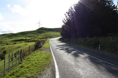 Strada campestre con la turbina ed il giacimento di vento Fotografie Stock