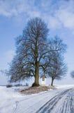 Strada campestre di inverno con un chappel del villaggio Fotografia Stock