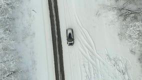 Strada campestre di inverno in una foresta nevosa, vista aerea con il fuco video d archivio
