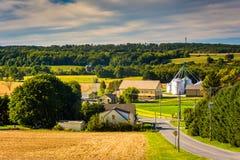 Strada campestre e vista del silo e del granaio su un'azienda agricola a York rurale C Immagini Stock Libere da Diritti