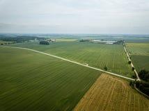 strada campestre in foresta verde e nell'immagine aerea del fuco dei campi fotografie stock