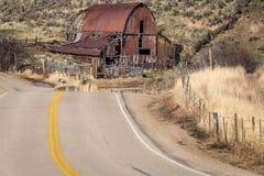Strada campestre iconica del granaio dell'Idaho e di bobina vicino ad un'azienda agricola Fotografie Stock Libere da Diritti
