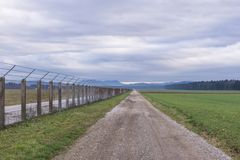 Strada campestre lunga che va diritto con il recinto a destra immagine stock libera da diritti