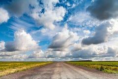 Strada campestre vuota dell'asfalto con il cielo nuvoloso drammatico Fotografie Stock Libere da Diritti