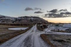 Strada che conduce comunque i plaines islandesi con la montagna nei precedenti Immagini Stock