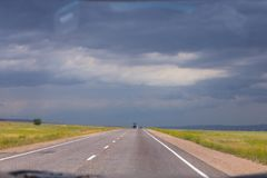 Strada che conduce nel fondo con le nuvole scure Immagini Stock Libere da Diritti
