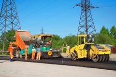 Strada che pavimenta con il camion, la macchina per la laminazione ed i lavoratori Fotografia Stock
