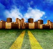 Strada con erba che entra in città Immagine Stock