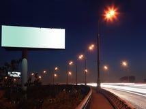 Strada con gli indicatori luminosi ed il grande tabellone per le affissioni in bianco immagini stock