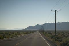 Strada con i pali di telegrafo immagini stock