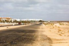 Strada con il deserto da un lato e una città d'altro canto Fotografia Stock Libera da Diritti