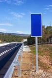 Strada con il palo blu del segno Fotografie Stock Libere da Diritti