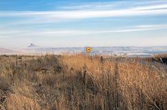 Strada con la bobina del segno limite di velocità attraverso il paesaggio asciutto di inverno Immagine Stock
