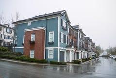 Strada con le case urbane residenziali nuovissime il giorno nuvoloso piovoso immagini stock libere da diritti