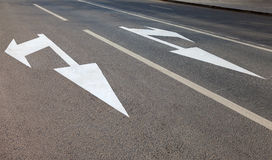Strada con le linee della marcatura e la direzione bianche di moto Immagine Stock Libera da Diritti