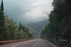 Strada con le montagne nebbiose Fotografia Stock