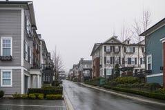 Strada con le nuove case urbane residenziali il giorno piovoso nuvoloso fotografie stock libere da diritti