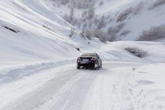 Strada con un'automobile nell'inverno nelle montagne fotografie stock