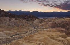 Strada conducente ad eternità alle montagne vita del deserto di tramonto nei precedenti in Death Valley fotografia stock libera da diritti