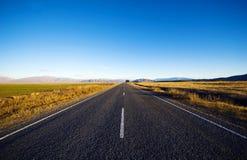Strada continua in uno scenico con le catene montuose lontano Immagini Stock