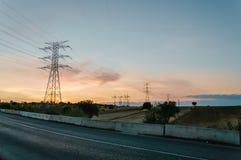 Strada contro le torri ad alta tensione al tramonto Fotografia Stock
