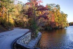 Strada Curvy della riva del lago circondata da acqua e dagli alberi variopinti fotografia stock