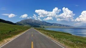 Strada dal cielo blu del lago Sayram Sailimu Fotografia Stock