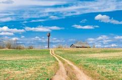 Strada del cielo nel campo che conduce alla torre del granaio e di acqua della tettoia del paesaggio rurale del villaggio Immagini Stock