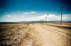 Strada del deserto attraverso l'Arizona con le poste di elettricità, S.U.A. fotografia stock