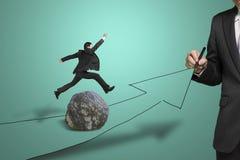 Strada del disegno dell'uomo d'affari con la freccia, un altro che salta sopra la roccia Immagine Stock