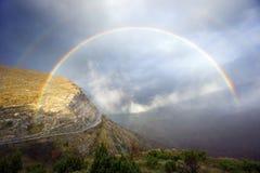 Strada del passo di montagna con le nuvole e l'arcobaleno tempestosi Fotografie Stock