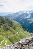 Strada dell'alpe circondata dalle alte montagne blu dell'alpe e dalle colline verdi Discesa ripida del dello Stelvio di Passo in  Fotografia Stock Libera da Diritti