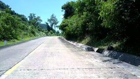 Strada dell'altopiano dopo la parete di pietra con la foresta densa verde archivi video