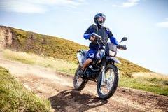 Strada dell'incrocio del motociclista di enduro all'alta velocità in montagne carpatiche Fotografia Stock