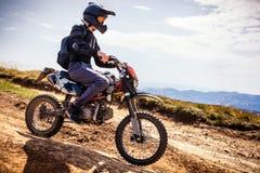Strada dell'incrocio del motociclista di enduro all'alta velocità in montagne carpatiche Immagini Stock Libere da Diritti
