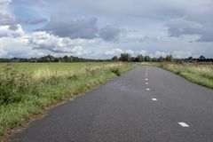 Strada della bicicletta, con le linee della strada, sotto un cielo nuvoloso immagini stock libere da diritti