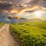Strada della ghiaia alle alte montagne al tramonto Immagine Stock
