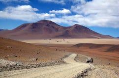 Strada della ghiaia nel deserto boliviano immagini stock