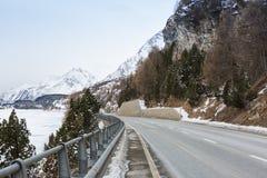 Strada della montagna in alpi svizzere ad un giorno di inverno nuvoloso Val Bregaglia, cantone Graubunden, Svizzera Fotografie Stock