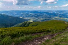 Strada della montagna che conduce alla discesa di alta collina contro il cielo blu Fotografie Stock Libere da Diritti