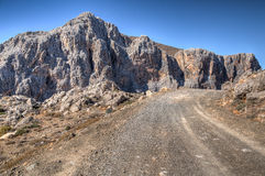 Strada della montagna che passa le scogliere rocciose irregolari Immagini Stock Libere da Diritti